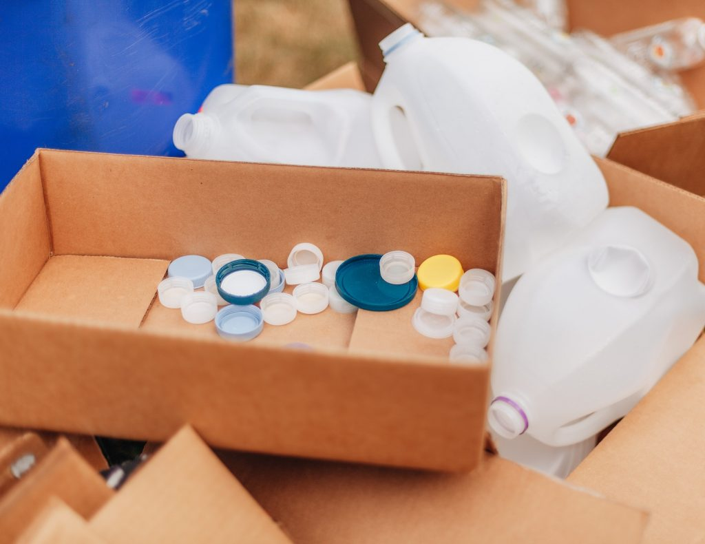 Recycling and environmentally friendly, bottle caps in card board box among plastic bottles